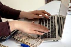 Бухгалтер девушки работая с деньгами на компьтер-книжке Стоковое фото RF