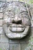 Будда смотрит на высекаенный в камне Стоковые Изображения