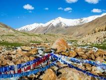 Буддийская молитва сигнализирует над малым рекой с голубым небом и горой на предпосылке Стоковые Фотографии RF