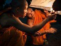 Буддийские монахи освещая вверх по горячему воздушному шару на Loi  Стоковая Фотография