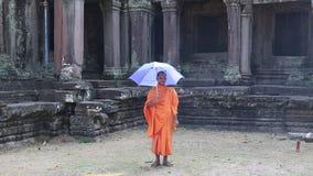 Буддийский монах в оранжевых одеждах с голубым зонтиком в комплексе виска Angkor Thom акции видеоматериалы