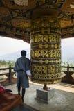 Буддийский паломник моля с молитвой катит внутри монастырь Chimi Lhakang, Бутан Стоковая Фотография RF
