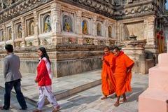 2 буддийских монаха идут за каменными стенами виска Стоковое Изображение