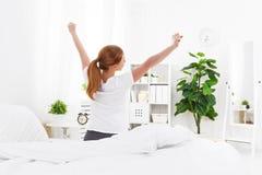 Будить утра молодой женщины в кровати Стоковые Изображения