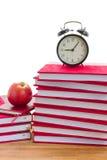Будильник и книги на таблице Стоковые Фото