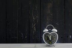Будильник на белой деревянной таблице Стоковое Фото
