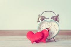 Будильник сердца и форма сердца на таблице Стоковая Фотография