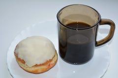 Булочка и кофе на белой плите Стоковое Фото