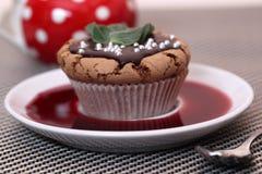 Булочка пирожного шоколада на белой плите с сиропом или вином клубники Стоковая Фотография RF