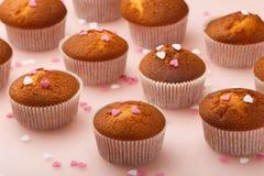 Булочки в бумажных формах и много малые сердца сахара на отраженной предпосылке Завтрак дня ` s валентинки Стоковые Изображения