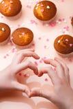 Булочки в бумажных формах и много малые сердца сахара на отраженной предпосылке Взгляд сверху Сердце рук и пальцев Стоковая Фотография