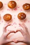 Булочки в бумажных формах и много малые сердца сахара на отраженной предпосылке Взгляд сверху Сердце рук и пальцев Стоковое Фото