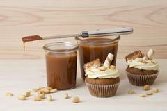 Булочки с посоленной карамелькой, украшенными печеньями и арахисами Стоковые Фото