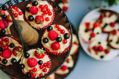 Булочки с сливк и ягодами лежат на двухуровневой стойке в зоне банкета свадьбы Взгляд сверху Стоковое Изображение