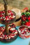 Булочки с сливк и ягодами лежат на двухуровневой стойке в зоне банкета свадьбы Стоковые Фотографии RF