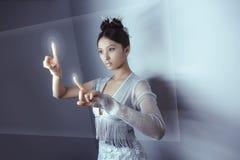Будущая принципиальная схема Hologram довольно азиатской женщины детенышей касающий цифровой Стоковые Фото