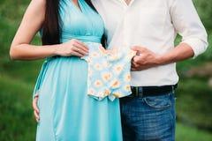 Будущие paremts держа детей одевают около беременного живота скрепляет болтами гайки семьи принципиальной схемы состава Стоковое Фото