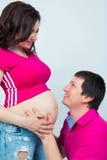 Будущий папа обнимает tummy и нежно смотрит его жену стоковое изображение
