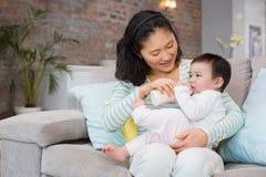 Будьте матерью давать молоко в бутылке к ее дочери Стоковые Изображения