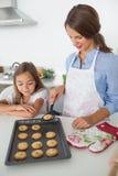 Будьте матерью давать домодельное печенье к ее дочери Стоковые Изображения RF