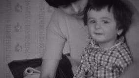 Будьте матерью ботинок платья на маленьком сыне в рубашке шотландки Улыбка младенца в камере Игра женщины с ребенком на кровати сток-видео