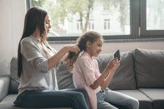 Будьте матерью волос заплетения ее дочери пока сидящ на софе Стоковые Фотографии RF