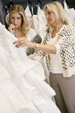 Будьте матерью выбирать платье свадьбы для молодой дочери в bridal магазине Стоковое Изображение