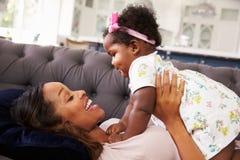 Будьте матерью лежать назад держащ ее дочь малыша na górze ее Стоковая Фотография