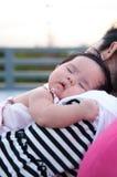 Будьте матерью держать ее newborn младенца в сексуальном платье пока она спало Младенец спит на ее плече матери на крыше Стоковые Фото