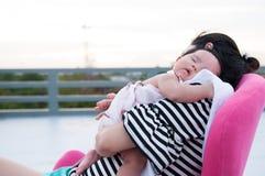 Будьте матерью держать ее newborn младенца в сексуальном платье пока она спало Младенец спит на ее плече матери на крыше Стоковая Фотография RF