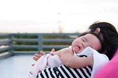 Будьте матерью держать ее newborn младенца в сексуальном платье пока она спало Младенец спит на ее плече матери на крыше Стоковое фото RF