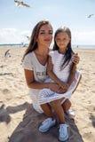 Будьте матерью держать дочь сидя на ее коленях на пляже стоковые фотографии rf
