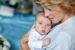 Будьте матерью держать newborn младенца в ее оружиях Стоковые Фото