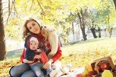 Будьте матерью играть с ее маленькой дочерью в осени стоковое изображение