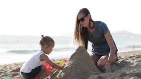 Будьте матерью играть с ее маленькой дочерью на пляже около воды на песке видеоматериал