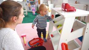 Будьте матерью играть с ее ребёнком в комнате с красочными блоками, шариками, кухней видеоматериал