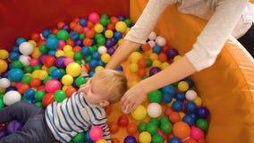 Будьте матерью играть с ее ребёнком в комнате с красочными блоками, шариками, кухней сток-видео