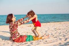 Будьте матерью игр с ее младенцем на пляже Стоковые Изображения RF
