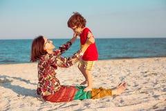 Будьте матерью игр с ее младенцем на пляже Стоковое Изображение