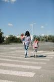 Будьте матерью и ее дети пересекая дорогу на пути к школе Стоковое фото RF