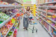 Будьте матерью и ее еда сына покупая на супермаркете стоковое изображение rf