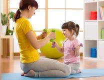 Будьте матерью и ее дочь ребенка делая тренировки фитнеса с гантелями Стоковая Фотография RF