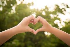 Будьте матерью и ее ребенок держа руки в форме сердца обрамляя на nat стоковые изображения