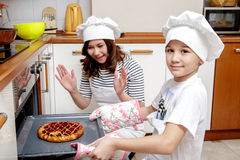 Будьте матерью и ее сын в белых шляпах шеф-повара подготавливая торт в кухне Стоковая Фотография
