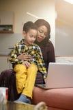 Будьте матерью и ее сын наблюдая что-то на компьтер-книжке Стоковая Фотография