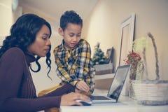 Будьте матерью и ее сын наблюдая что-то на компьтер-книжке Стоковое фото RF