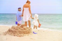 Будьте матерью и 2 дет играют с песком на пляже Стоковые Фото