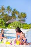 Будьте матерью и 2 дет играя с песком на тропическом Стоковая Фотография RF