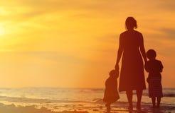 Будьте матерью и 2 дет идя на пляж захода солнца Стоковые Изображения