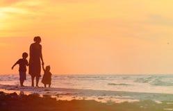 Будьте матерью и 2 дет идя на пляж захода солнца Стоковое Изображение